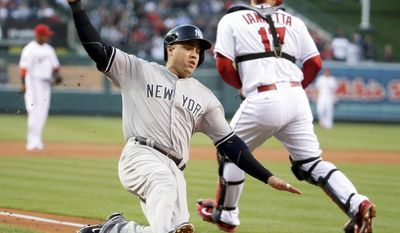 New York Yankees' Carlos Beltran, left, scores past Los Angeles Angels catcher Chris Iannetta on a sacrifice fly by Yangervis Solarte during the first inning of a baseball game in Anaheim, Calif., Wednesday, May 7, 2014. (AP Photo/Chris Carlson)