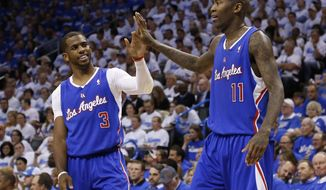 Los Angeles Clippers guard Chris Paul (3) high fives teammate Jamal Crawford (11) in the second quarter of Game 2 of the Western Conference semifinal NBA basketball playoff series against the Oklahoma City Thunder in Oklahoma City, Wednesday, May 7, 2014. (AP Photo/Sue Ogrocki)