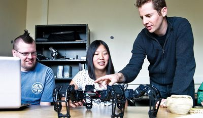 In this April 30, 2014 photo, University of Wyoming assistant professor of computer science Jeff Clune, right, points out various components of a test model robot to undergraduate student Tyler Hughes, left, and Laramie High School student Jingyu Li, at the Artificial Intelligence Laboratory in Laramie, Wyo. (AP Photo/Laramie Daily Boomerang, Jeremy Martin)