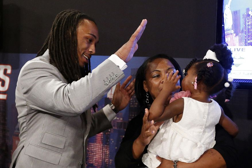 Calvin Pryor, from Louisville, high-fives with his 2-year-old daughter Jayle Exum and mother Monique Turrell after being selected 18th overall by the New York Jets in the first round of the NFL football draft, Thursday, May 8, 2014, at Radio City Music Hall in New York. (AP Photo/Jason DeCrow)