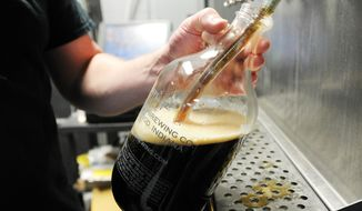 In this April 27, 2014 photo, Andrew Groves fills a growler with beer at Planetary Brewing Company in Greenwood, Ind.  As recently as 2008, Indiana had fewer than 10 craft breweries. But as craft beers have become more popular, more and more small-batch brewers are selling their creations to the public.  By the end of April, 71 breweries were in operation in the state, with another 32 planned to open this year. Local enthusiasts sell double India pale ales and bourbon-barrel stouts, Belgian dubbels and fruit-infused lambics.  Johnson County is catching up. Three craft brewers are open in the county, with another coming online by the end of the month.  (AP Photo/Daily Journal,  Scott Roberson)