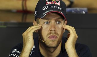 Red Bull driver Sebastian Vettel of Germany touches his temples during a news conference at the Catalunya racetrack in Montmelo, near Barcelona, Spain, Thursday, May 8, 2014. The Formula One race will be held on Sunday. (AP Photo/Luca Bruno)