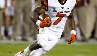 FILE - In this Nov. 16, 2013, file phot, Oregon State wide receiver Brandin Cooks (7) carries the ball during the second half of an NCAA college football game against Arizona State in Tempe, Ariz. Cooks was selected in the first round, 20th overall, by the New Orleans Saints in the NFL draft on Thursday, May 8, 2014. (AP Photo/Rick Scuteri)