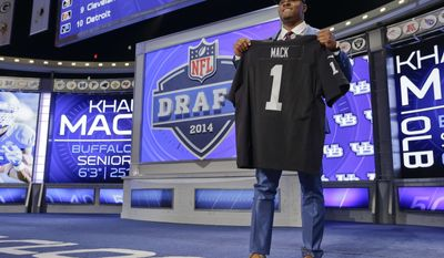 Buffalo linebacker Khalil Mack, right, poses for photos with NFL commissioner Roger Goodell after being selected by the Oakland Raiders as the fifth pick in the first round of the 2014 NFL Draft, Thursday, May 8, 2014, in New York. (AP Photo/Craig Ruttle) . (AP Photo/Craig Ruttle)