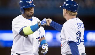 Toronto Blue Jays' Juan Francisco, left, celebrates a single with first base coach Tim Leiper during the third inning of a baseball game against the Philadelphia Phillies in Toronto on Thursday, May 8, 2014. (AP Photo/The Canadian Press, Darren Calabrese)