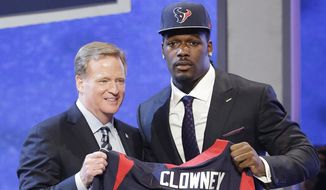 South Carolina defensive end Jadeveon Clowney hold up the jersey for the Houston Texans first pick of the first round of the 2014 NFL Draft with NFL commissioner Roger Goddell, Thursday, May 8, 2014, in New York. (AP Photo/Frank Franklin II)