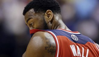 Washington Wizards' John Wall wipes his face during the second half of game 2 of the Eastern Conference semifinal NBA basketball playoff series against the Indiana Pacers, Wednesday, May 7, 2014, in Indianapolis. Indiana won 86-82. (AP Photo/Darron Cummings)