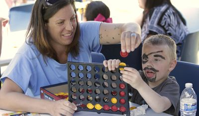 In this photo taken May 3, 2014, inmate Lisa Mercuri plays a game with her son, Noah, 4, during his visit to the Folsom Women's Facility in Folsom Calif.  Mercuri, who is serving time for forgery and fraud, had the chance to spend time with her son through a nonprofit program called Get on the Bus that arranges for children of inmates to visit their parents in California prisons around Mother's and Father's days. (AP Photo/Rich Pedroncelli)