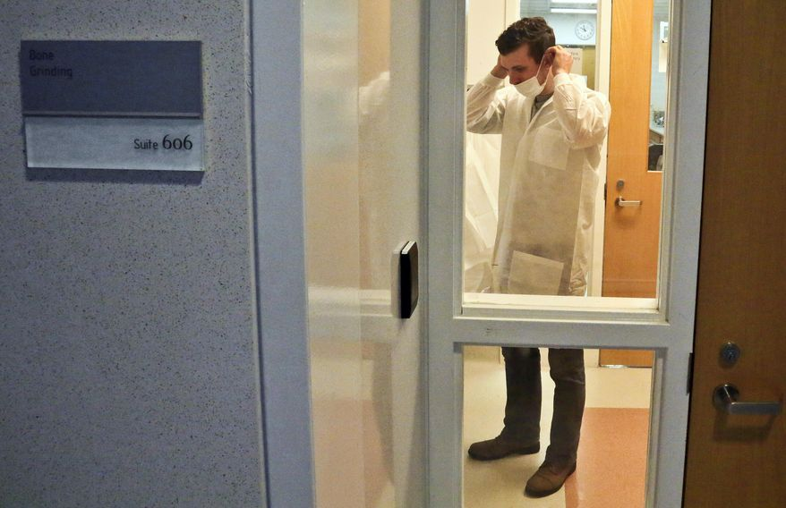 In this April 15, 2014 photo, Michael Mosco, a criminalist, prepares to enter the bone grinding room at the Office of Chief Medical Examiner in New York. The room is central to the examination of bone DNA from those who died on Sept. 11, 2001. Forensic scientists are still trying to match the bone with DNA from victims who have never been identified. (AP Photo/Bebeto Matthews)