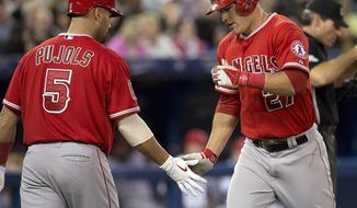 Los Anglees Angels Mike Trout, right, is congratulated by teammate Albert Pujols after hitting a solo home run off Toronto Blue Jays starting pitcher Dustin McGowan during the third inning of a baseball game in Toronto on Friday May 9, 2014. (AP Photo/The Canadian Press, Frank Gunn)