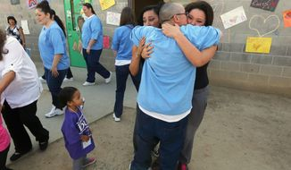 In this photo taken May 3, 2014, inmate Catherine La France, center, greets her daughters, Summer, 14, left, and Samantha, 18, as her granddaughter Arianna, 3,  left, looks on at the Folsom Women's Facility in Folsom Calif. La France, had the chance to spend time with her family through a nonprofit program called Get on the Bus that arranges for children of inmates to visit their parents in California prisons around Mother's and Father's days. La France, who had celebrated her 39th birthday two days earlier, said the visit was her birthday and Mother's Day present. (AP Photo/Rich Pedroncelli)