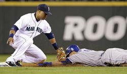 Kansas City Royals' Lorenzo Cain, right, slides into a tag by Seattle Mariners second baseman on an attempted stolen base attemptin the seventh inning of a baseball game Thursday, May 8, 2014, in Seattle. (AP Photo/Elaine Thompson)