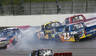 Todd Bodine (30) spins out in front of Brendan Gaughan (77), Johnny Benson (23) and Timothy Peters (17) during first lap of the NASCAR Camping World Truck Series race at Kansas Speedway in Kansas City, Kan., Friday, May 9, 2014. (AP Photo/Colin E. Braley)