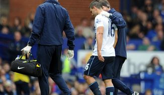 Manchester City's Sergio Aguero, center, leaves the field after sustaining an injury during their English Premier League soccer match against Everton at Goodison Park in Liverpool, England, Saturday May 3, 2014. (AP Photo/Clint Hughes)