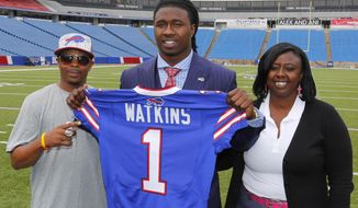 Buffalo Bills first round draft pick Sammy Watkins poses for photos with his father James McMiller, left, and mother Nicole McMiller at Ralph Wilson Stadium in Orchard Park, N.Y., Friday, May 9, 2014. (AP Photo/Bill Wippert)