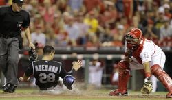 Colorado Rockies' Nolan Arenado (28) scores on a double hit by Justin Morneau in the ninth inning of a baseball game against the Cincinnati Reds, Friday, May 9, 2014, in Cincinnati. Reds' Brayan Pena, right, catches as umpire Cory Blaser makes the call. Cincinnati won 4-3. (AP Photo/Al Behrman)
