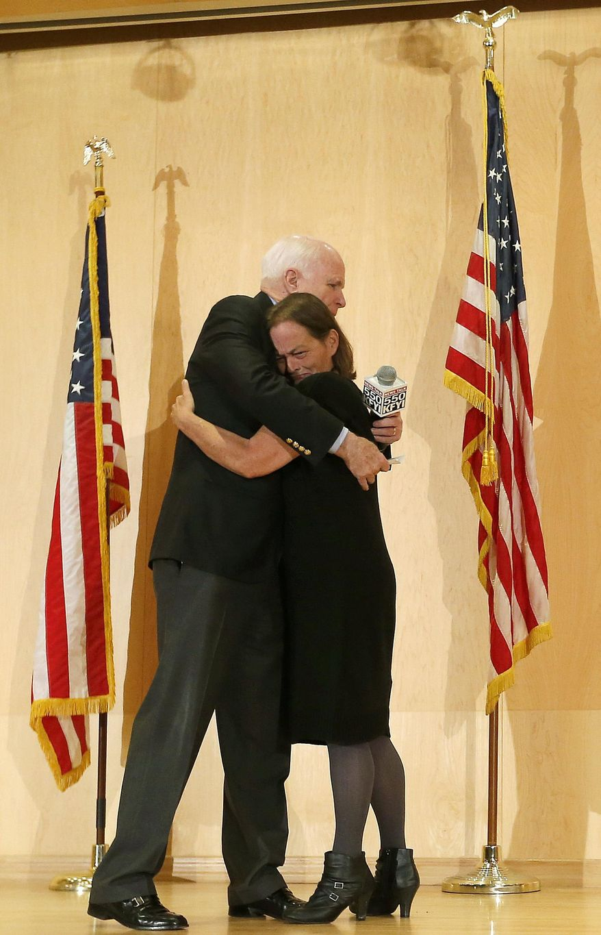 Sen. John McCain embraces Gabriel Basso after she shared how her veteran husband died during a forum with veterans on Friday, May 9, 2014, in Phoenix. McCain was discussing lapses in care at the Phoenix Veterans Affairs hospital that prompted a national review of operations around the country. (AP Photo/Matt York)