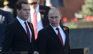 Russian President Vladimir Putin, right, and Prime Minister Dmitry Medvedev arrive to attend a Victory Day parade, which commemorates the 1945 defeat of Nazi Germany, in Moscow, Russia, Friday, May 9, 2014. Russia marked the Victory Day on May 9 holding a military parade at Red Square in Moscow. (AP Photo/RIA-Novosti, Alexei Nikolsky, Presidential Press Service)