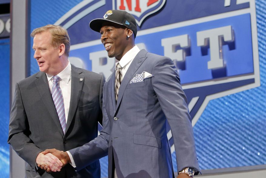 USC wide receiver Marqise Lee, right is greeted by NFL commissioner Roger Goodell  after being selected as the 39th pick by the Jacksonville Jaguars in the second round of the 2014 NFL Draft, Friday, May 9, 2014, in New York. (AP Photo/Jason DeCrow)