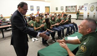 Texas state Sen. Jose Rodriguez greets Border Patrol Division Chief Michael Przybyl after addressing high school students that graduated from at-risk youth program at the Border Patrol station in El Paso, Texas, Friday, May 09, 2014. Twelve teenagers referred by truancy court graduated Friday from the five-week REAL program in which Border Patrol agents mentor them through physical training, community service and presentations at other local institutions like a jail tour.  (AP Photo/Juan Carlos Llorca)