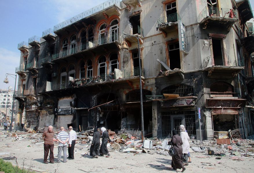 Syrian civilians return to their neighborhood in the old city of Homs, Syria on Friday, May 9,  2014, where bulldozers cleared rubble from the streets of battle-scarred districts in the central Syrian city after government troops entered the last rebel-held neighborhoods as part of an agreement that also granted opposition fighters safe exit from the city. (AP Photo)