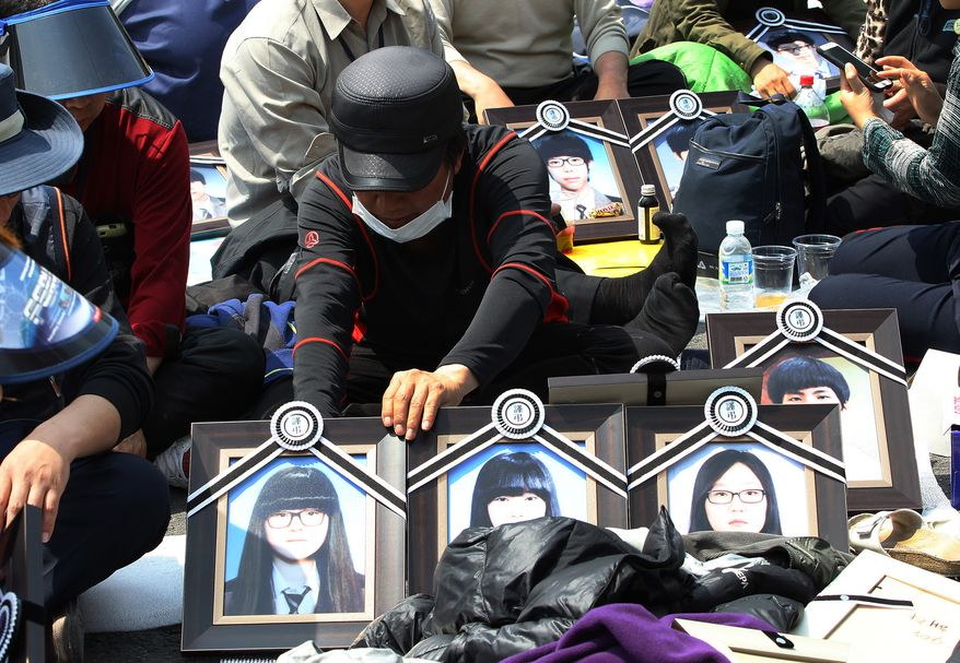 A family member of the victims of the sunken ferry Sewol displays portraits of victims near the presidential Blue House in Seoul, South Korea, Friday, May 9, 2014. Family members of the victims in the ferry sinking marched to the presidential Blue House in Seoul early Friday calling for a meeting with President Park Geun-hye but ended up sitting on streets near the presidential palace after police officers blocked them. Park's office said a senior presidential official plans to meet them later Friday. (AP Photo/Ahn Young-joon)
