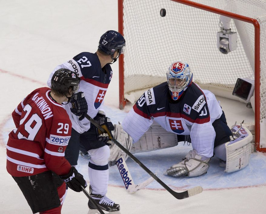Canada's Nathan MacKinnon watches the puck enter the net behind Slovakia goalie Jan Laco as teammate Ladislav Nagy looks on during third period action at the IIHF Ice Hockey World Championship in Minsk, Belarus, on Saturday, May 10, 2014.  (AP Photo/The Canadian Press, Jacques Boissinot)