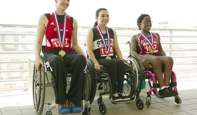 Winners of the University Interscholastic League's first-ever girls wheelchair seated shot put event, from left, Abby Dunkin, from New Braunfels, gold; Kortney Boldt, from Steele High School in Cibolo, silver, and Brandi Smith, from Rowlett, bronze, sit together after competing in the UIL Track and Field State Championships at the Mike A. Myers Stadium at The University of Texas at Austin on Saturday, May 10, 2014. (AP Photo/Austin American-Statesman, Ralph Barrera)