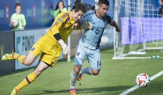 Sporting Kansas City's Dom Dwyer, right, and Montreal Impact goalkeeper Troy Perkins battle for the ball during the second half of an MLS soccer game in Montreal, Saturday, May 10, 2014. (AP Photo/The Canadian Press, Graham Hughes)