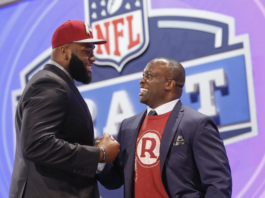 Virginia tackle Morgan Moses greets former Washington Redskins' linebacker London Fletcher after being selected by the Redskins as the 66th pick during the third  round of the 2014 NFL Draft, Friday, May 9, 2014, in New York. (AP Photo/Jason DeCrow)