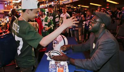 New York Jets linebacker Demario Davis, right, greets Chris Martinez of Brooklyn, N.Y., while signing autographs during the fourth round of the 2014 NFL Draft, Saturday, May 10, 2014, in New York. (AP Photo/Julie Jacobson)