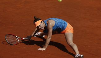 Simona Halep from Romania falls as she returns the ball during a Madrid Open tennis tournament semifinal match against Petra Kvitova from the Czech Republic in Madrid, Spain, Saturday, May 10, 2014. (AP Photo/Andres Kudacki)
