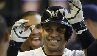 Milwaukee Brewers' Aramis Ramirez reacts in the dugout after his home run against the New York Yankees in the third inning of a baseball game on Saturday, May 10, 2014, in Milwaukee. Brewers' Carlos Gomez, background, also reacts. (AP Photo/Jeffrey Phelps)