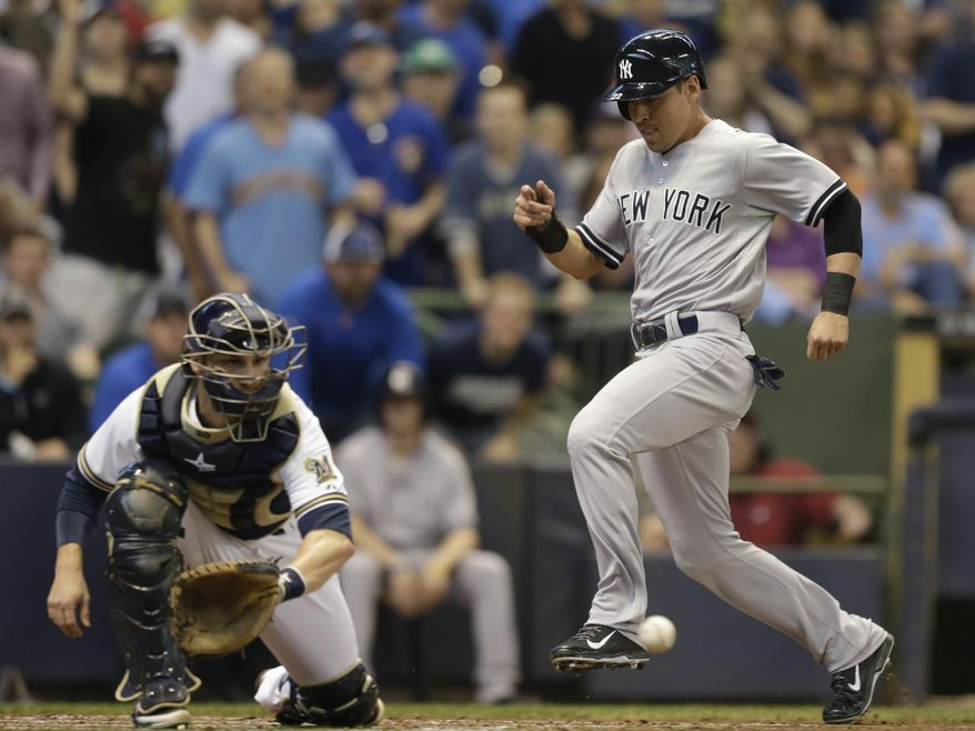 New York Yankees' Jacoby Ellsbury, right, scores ahead of the tag by Milwaukee Brewers' Jonathan Lucroy in the third inning of a baseball game Saturday, May 10, 2014, in Milwaukee. (AP Photo/Jeffrey Phelps)