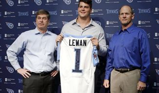 Tennessee Titans first round draft pick Taylor Lewan, an offensive lineman from Michigan, poses with Titans general manager Ruston Webster, left, and head coach Ken Whisenhunt, right, at an NFL footblal news conference Friday, May 9, 2014, in Nashville, Tenn. Lewan was the 11th overall pick in the NFL football draft on Thursday. (AP Photo/Mark Humphrey)