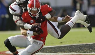 FILE - In this Sept. 7, 2013, file photo, South Carolina defensive end Jadeveon Clowney (7) tackles Georgia quarterback Aaron Murray (11) during the first half of an NCAA football game in Athens, Ga. Clowney finished last season with 11 1/2 tackles for loss and three sacks after getting 23 1/2 and 13 in 2012. He is a top prospect in the upcoming NFL draft. (AP Photo/John Bazemore, File)