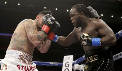 Bermane Stiverne, right, hits Chris Arreola during their rematch for the WBC heavyweight boxing title in Los Angeles, Saturday, May 10, 2014. Stiverne won the title. (AP Photo/Chris Carlson)