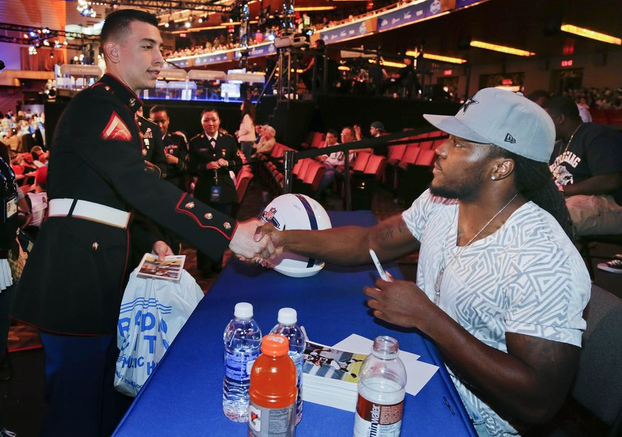 New York Jets running back Chris Ivory, right, greets Lance Cpl. Julio Ortiz while signing autographs for fans during the fourth round of the 2014 NFL Draft, Saturday, May 10, 2014, in New York. (AP Photo/Julie Jacobson)