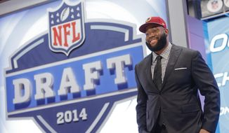 Virginia tackle Morgan Moses poses for photos after being selected as the 66th pick by the Washington Redskins during the third  round of the 2014 NFL Draft, Friday, May 9, 2014, in New York. (AP Photo/Jason DeCrow)