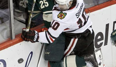 Chicago Blackhawks left wing Patrick Sharp (10) checks Minnesota Wild defenseman Jonas Brodin (25) into the boards as they battle for the puck during the first period of Game 4 of an NHL hockey second-round playoff series in St. Paul, Minn., Friday, May 9, 2014. (AP Photo/Ann Heisenfelt)