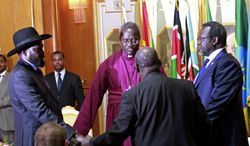 South Sudan's President Salva Kiir, left, and rebel leader Riek Machar, right, shake hands and pray before signing an agreement of the cease-fire of the conflict in South Sudan in Addis Ababa, Ethiopia,  Friday, May 9, 2014. (AP Photo/Elias Asmare) ** FILE **