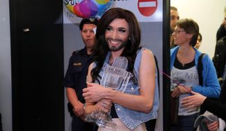 Austrian singer Conchita Wurst  arrives with the trophy at the  airport in Vienna Sunday May 11, 2014.  Bearded drag queen Conchita Wurst has made a triumphant return to Austria after winning the Eurovision Song Contest in Copenhagen Saturday,  in what the country's president called a victory for tolerance in Europe.  (AP Photo/Ronald Zak)