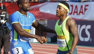 Justin Gatlin, left, of the U.S. greets fellow countryman Mike Rodgers after the men's 100 meters race at the Golden Grand Prix Field and Track in Tokyo, Sunday, May 11, 2014. Gatlin won the men's 100 meters in a time of 10.02 seconds.(AP Photo/Shizuo Kambayashi)