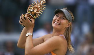 Maria Sharapova from Russia celebrates her victory holding her trophy after a Madrid Open tennis tournament final match against  Simona Halep from Romania in Madrid, Spain, Sunday, May 11, 2014. (AP Photo/Andres Kudacki)