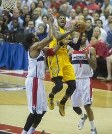 Indiana's Paul George (24) goes up for the basket while defended by Wizards' Nene (42) and Trevor Ariza (1) in the first quarter as the Washington Wizards host the Indiana Pacers for Game 4 of the Eastern Conference semifinal playoff series at the Verizon Center in Washington, DC, Sunday, May 11, 2014. (Photo Rod Lamkey Jr.)