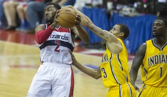 Wizards' John Wall (2) is defended by Pacers' George Hill (3) as he makes a pass under the basket in the third quarter as the Washington Wizards host the Indiana Pacers for Game 4 of the Eastern Conference semifinal playoff series at the Verizon Center in Washington, DC, Sunday, May 11, 2014. (Photo Rod Lamkey Jr.)