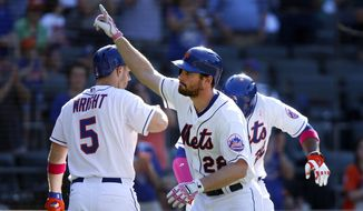 New York Mets' Daniel Murphy, center, celebrates after hitting a two-run home run during the ninth inning of a baseball game against the Philadelphia Phillies, Sunday, May 11, 2014, in New York. (AP Photo/Jason DeCrow)