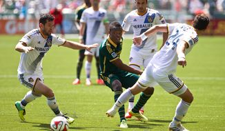 Los Angeles Galaxy defender Dan Gargan, left, Portland Timbers midfielder Steve Zakuani, center, and Los Angeles Galaxy midfielder Stefan Ishizaki (24) battle for possession Sunday, May 11, 2014, at Providence Park in Portland, Oregon. (AP Photo/The Oregonian, Thomas Boyd)  MAGS OUT; TV OUT; LOCAL TV OUT; LOCAL INTERNET OUT; THE MERCURY OUT; WILLAMETTE WEEK OUT; PAMPLIN MEDIA GROUP OUT