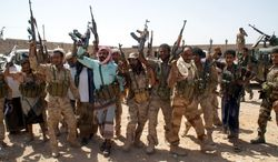 In this photo provided by Yemen's Defense Ministry, Yemen's army soldiers hold up their weapons at an area seized from al-Qaida in the southeastern province of Shabwa, Yemen, Thursday, May 8, 2014. Yemeni armed forces on Thursday swept al-Qaida fighters out of a district in the country's south, one of the main goals of the major offensive waged by the military the past two weeks, the Defense Ministry said, amid fears of retaliatory attacks which officials say prompted the closure of the US embassy in the capital as a precaution. (AP Photo/Yemen's Defense Ministry)