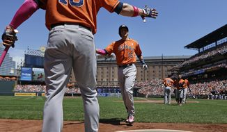 Houston Astros' Jason Castro, center, jogs off the field toward teammate Marc Krauss after hitting a three-run home run in the first inning of a baseball game against the Baltimore Orioles, Sunday, May 11, 2014, in Baltimore. (AP Photo/Patrick Semansky)